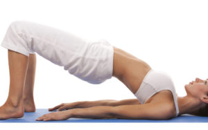 Supported bridge pose to assist with fertility