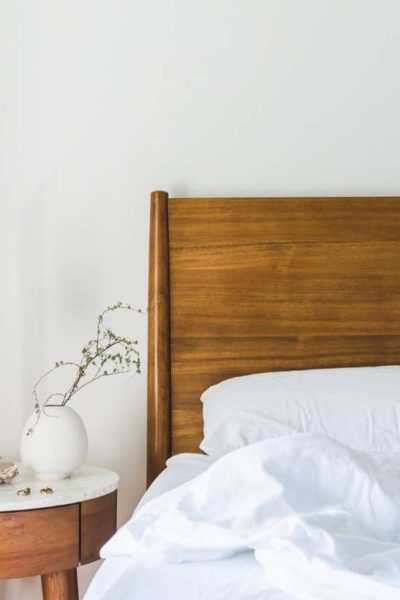 Unmade bed with vase on bedside table