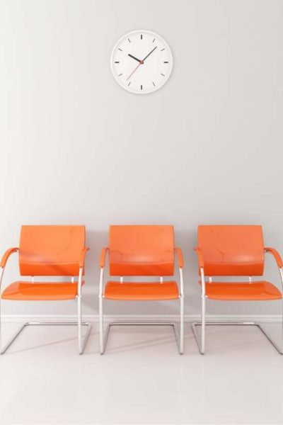 Orange chairs and white clock in waiting room
